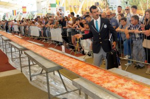 Judge of the Guinness World Records Lorenzo Veltri checks the length of a pizza at the Expo 2015 world's fair in Rho, near Milan, Saturday, June 20, 2015.  More than 60 of Italy's best pizza-makers worked through the night to create a 1.59545 kilometers, or nearly a mile long pizza at Milan's world fair. Their toil was rewarded with a proclamation by Guinness World Records judge Saturday that it was the world's longest pizza. Expo organizers said the record-setting pie, made with 1.5 tons of mozzarella and 2 tons of tomato sauce, weighed some 5 tons in all. (Daniele Mascolo/ANSA via AP)